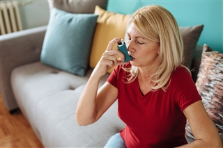 adult woman using an asthma inhaler